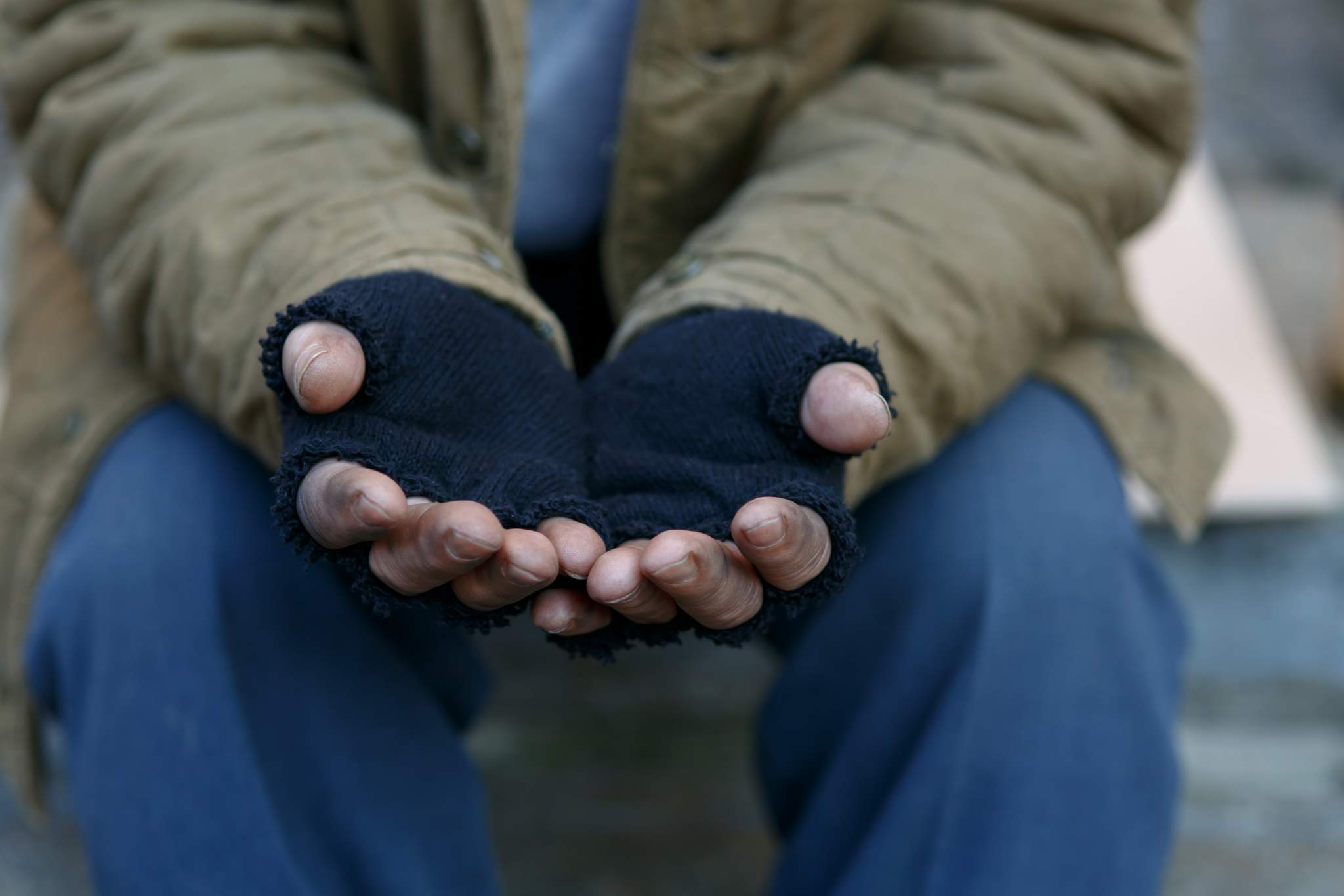 Homeless man holding hands out.