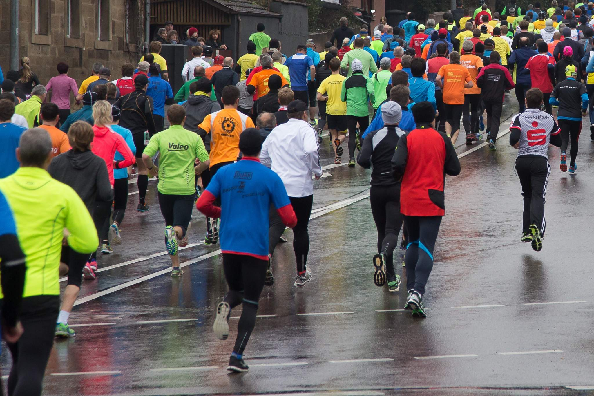 Large group of runners running down the street in a marathon.